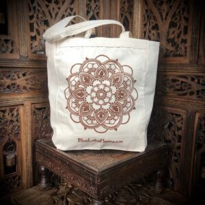 Cream colored cotton canvas tote bag with brown mandala screen print