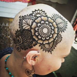 Henna tattoo floral design on side of female scalp