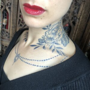 Jagua tattoo stain of peony and chain design on female neck and chest