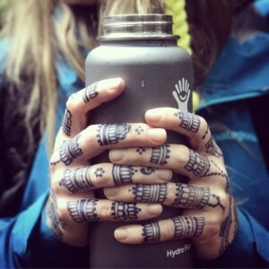 Jagua tattoo stain on fingers of female hand holding flask