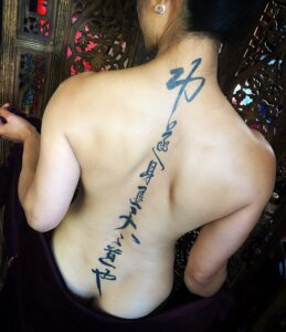 Jagua tattoo stain of Chinese characters down female spine