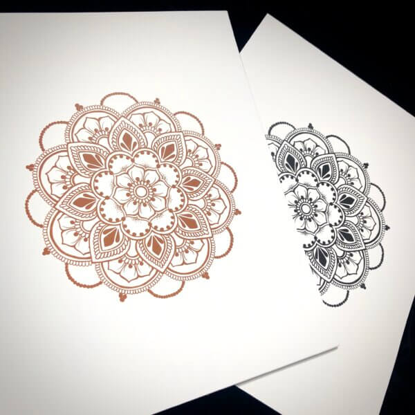 Closer shot of prints of two mandala images, one in henna brown color, the other in deep jagua blue color
