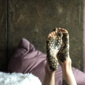 Floral jagua tattoo design on soles of female feet in boudoir setting