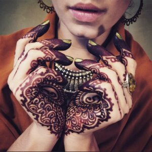 Deep henna tattoo palm stain on female model with exotic jewelry