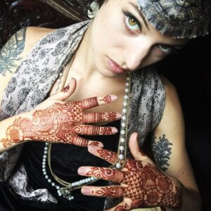 Flapper girl with henna tattoo stain on her hands in a glove style design