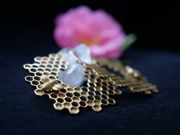 Honeycomb brass earrings with a small bee on them