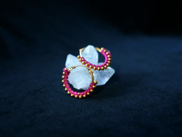 metal earrings wrapped with pink thread