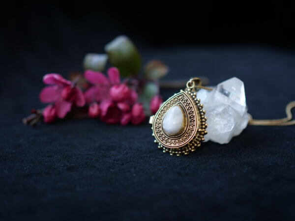 Tear drop shaped locket with rainbow moonstone setting