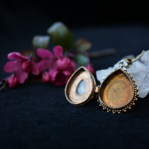 Tear drop shaped locket with rainbow moonstone setting