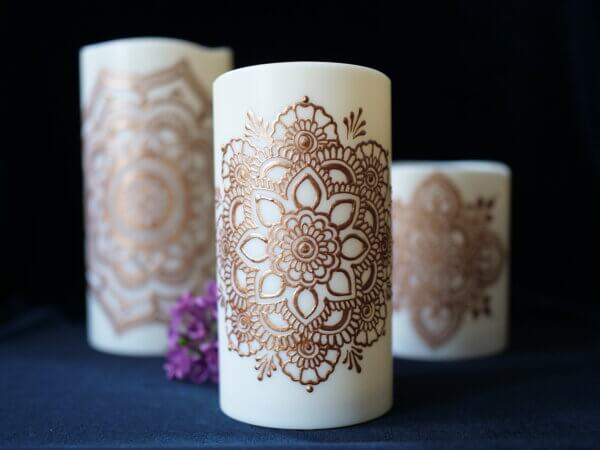 set of three led candles in varying size painted with mandalas in copper metallic paint