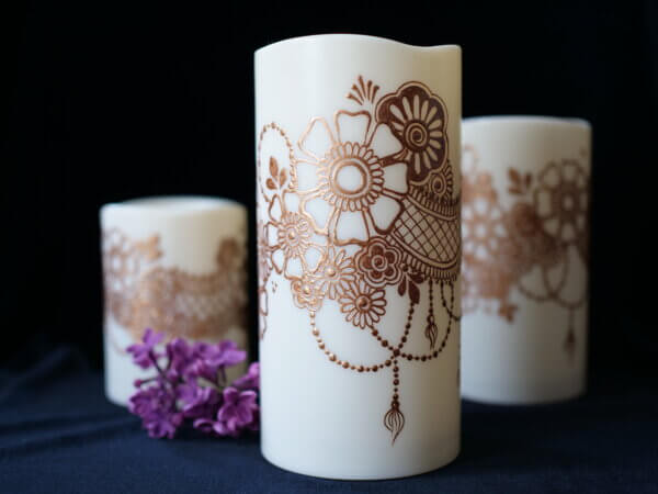 Set of three LED candles of various size, hand painted in copper metallic paint