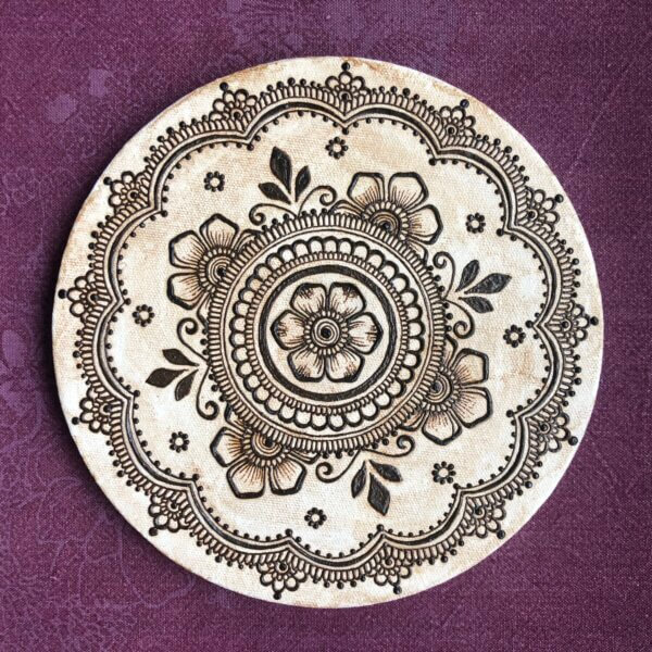 circular canvas with floral mandala painted in henna paste