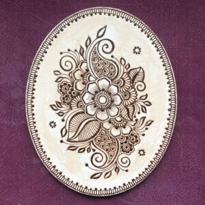 oval canvas with floral painting done in henna paste