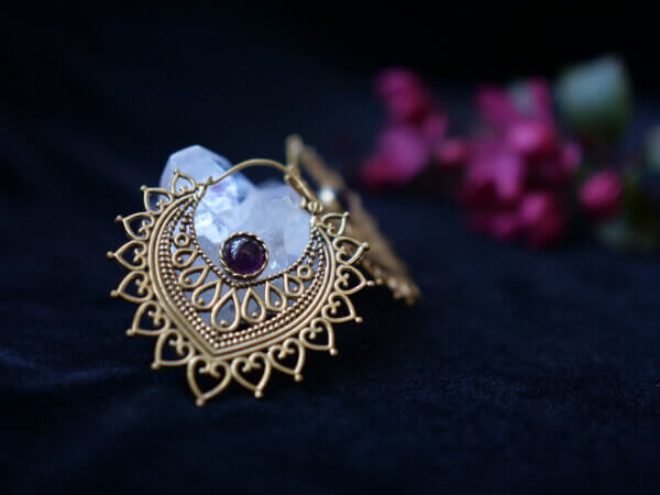 Amethyst earrings set in brass shaped like a lotus petal with mehndi style designs